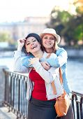 stock photo of hug  - Two beautiful girls laughing and hug in the city outdoor - JPG