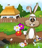 stock photo of farmhouse  - Bunny with a basket of Easter eggs and flowers in a meadow near the farmhouse with a thatched roof - JPG