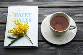 foto of mimosa  - Fairy Tales book with cup of tea and sprig of mimosa on wooden background - JPG