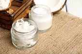 picture of sackcloth  - Coconut with jars of coconut oil and  cosmetic cream on sackcloth background - JPG