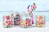 foto of sweetie  - Multicolor candies in glass jars on color wooden background - JPG
