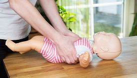 stock photo of baby doll  - Woman performing CPR on baby training doll with two hands compressions - JPG