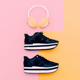 stock photo of vanilla  - Trendy white headphones and sneakers on vanilla background - JPG