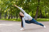 image of extend  - Smiling beautiful sporty young woman working out on road doing warming up lunge exercise Utthita Parsvakonasana Extended Side Angle Pose full length - JPG