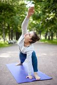 picture of extend  - Serene beautiful sporty young woman working out in park alley doing warming up stretching exercise standing in Utthita Parsvakonasana Extended Side Angle Pose full length - JPG