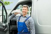 stock photo of coil  - Happy Repairman With White Cable Coil Standing In Front Of Van - JPG