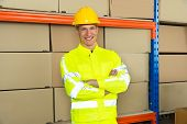 stock photo of warehouse  - Portrait Of Happy Male Warehouse Worker With Arms Crossed In Warehouse - JPG