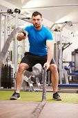 picture of battle  - Young man working out with battle ropes at a gym - JPG