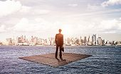 stock photo of raft  - businessman standing on raft and looking to city - JPG