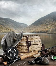 foto of fly rod  - Fly rod with creel and equipment on wood table - JPG