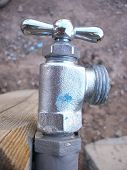 stock photo of bib tap  - Shiny hose bib (water faucet) in a right-discharge orientation. Body has bright but textured finish; handle is smooth shiny chrome.