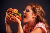 Woman eating sandwich. Girl with pleasure eats burger after diet. She opened her mouth, holding a ha poster