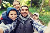 technology, travel, tourism, hike and people concept - happy family with backpacks taking selfie and poster