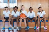Portrait of school kids sitting in basketball court at school poster