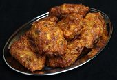 Indian Onion Bhajis on stainless steel tray.