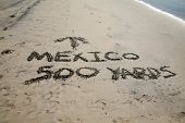 Words in sand. Mexico 500 yards with Arrow pointing towards Mexico written in the sand at the border poster