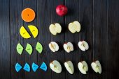 colorful math fractions and apples as a sample on brown wooden background or table. interesting math poster
