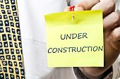 Under construction post it in business man hand