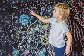 Little Boy Pointing Space, Planets And Stars On The Wall poster