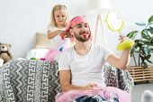 Adorable Little Daughter In Tutu Skirt Playing With Happy Father In Pink Wig Looking At Mirror poster
