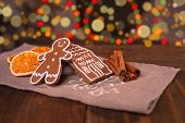 Christmas Homemade Gingerbread Cookies On Wooden Table, Slices Of Dry Orange And Colored Lights On B poster