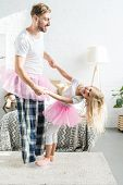 Happy Father And Little Daughter In Pink Tutu Skirts Holding Hands And Dancing At Home poster