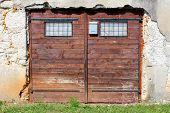 Garage Doors Made Of Small Wooden Boards With Faded Brown Color And Two Small Windows Protected With poster