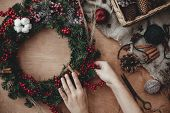 Rustic Christmas Wreath Flat Lay. Hands Holding Fir Branches, Red Berries And Pine Cones,thread, Sci poster