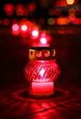 Closeup of red burning votive candle in lights background
