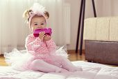 Beautiful Little Baby Girl Wearing Pink Tutu Skirt, Sitting On A Duvet On The Nursery Floor, Playing poster