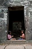 SIEM REAP, CAMBODIA - CIRCA JANUARY 2009: Two young girls make souvenir necklaces at Angkor Wat temp