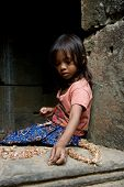 SIEM REAP, CAMBODIA - CIRCA JANUARY 2009: A young unidentified girl makes a souvenir necklace at Ang