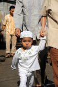 JAKARTA, INDONESIA - SEPTEMBER 20: Parents take their young child to the mosque for prayer on Hari Raya, the end of a month of fasting called Ramadan September 20, 2009 in Jakarta.