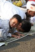 JAKARTA, INDONESIA - SEPTEMBER 20: A Muslim boy prays with his father outside a mosque in Jakarta on