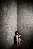 stock photo of domestic violence  - Abused woman in the corner of a stairway comforting herself - JPG