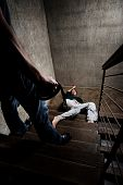 Battered woman lies lifelessly at the bottom of stairs, a conceptual shoot depicting the effects of