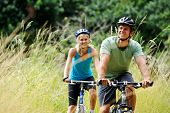stock photo of exercise bike  - Happy couple riding bicycles outside - JPG
