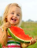 stock photo of watermelon slices  - Adorable blonde girl eats a slice of watermelon outdoors - JPG