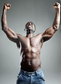 Well-built muscular black man with arms raised in studio