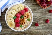 Delicious And Healthy Oatmeal With Banana, Raspberries, Nuts. Healthy Breakfast. Fitness Food. Prope poster