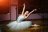 Charming Little Girl Ballet Dancer In White Tutu Performing Ballet Poses On The Floor In Dance Studi poster