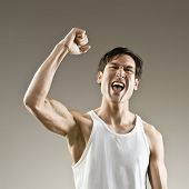 Muscular man making fist and cheering