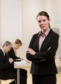 Serious businesswoman posing with co-workers meeting in conference room behind her