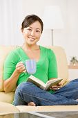 Woman relaxing on sofa in livingroom enjoying reading a book and drinking coffee