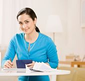 Woman writing check from checkbook to pay monthly bills