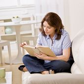pic of reading book  - Relaxed woman sitting on sofa in livingroom enjoying reading book - JPG