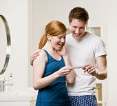 Excited, happy couple in bathroom viewing positive pregnancy test