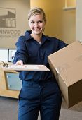 Friendly delivery woman in uniform presenting shipping receipt and holding cardboard box