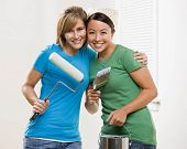 Self-sufficient friends painting with paint roller and paint brush and paint can and renovating home