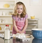 Cute blond little girl making bread in the kitchen. Milk bottle, bowl and eggs on the counter. Squar